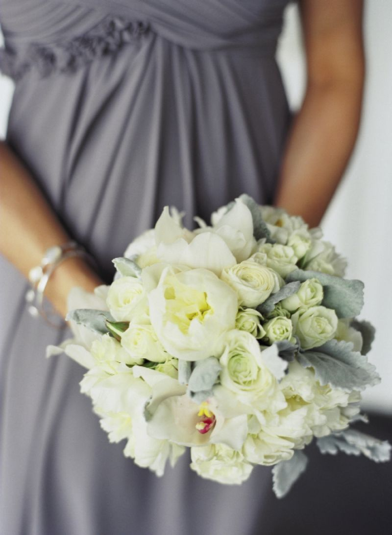 QUITE THE HANDFUL: Bridesmaids carried white ranunculus, cream-colored spray roses, and ivory peonies accented with lamb's ears and Dusty Miller.