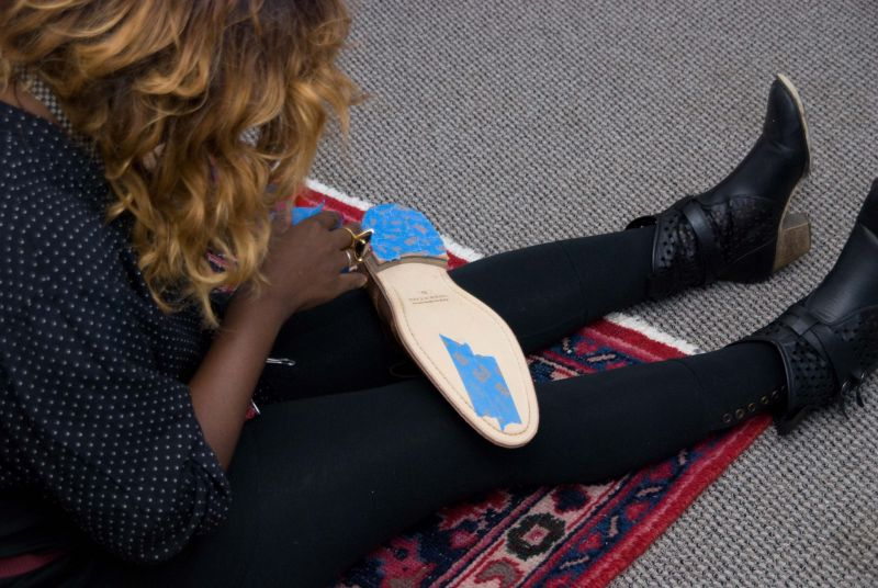 Ayoka covers the bottom of shoes with painter's tape so as to not damage the soles.