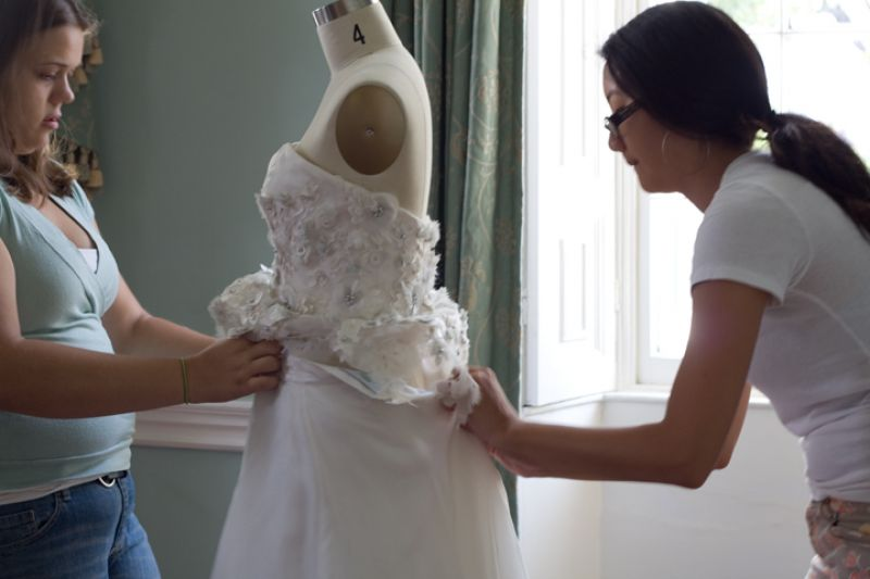 "The mannequin was a size 4 and ""Versailles"" fit it like a glove, but still, Kristy needed a little help from Charleston Weddings editor Melissa Bigner to zip it up."