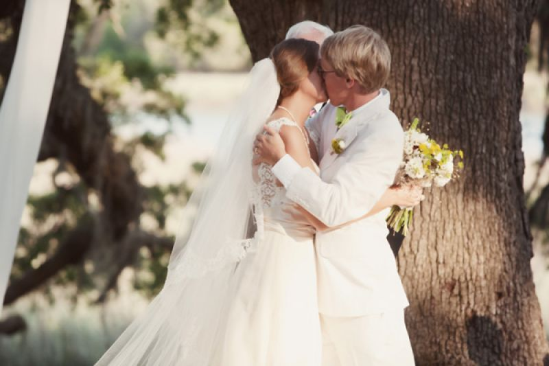 "SEALED WITH A KISS: The couple sealed their ""I do's"" with a kiss in front of the ancient oak tree."