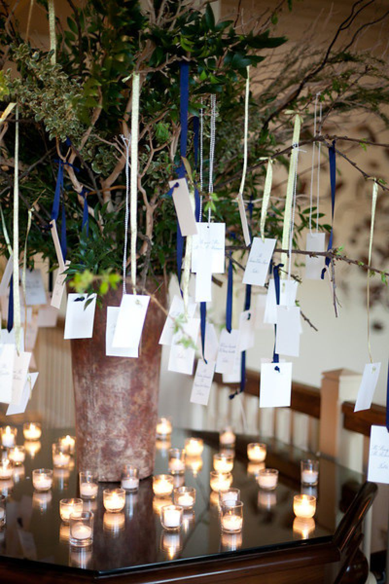 HANGING OUT: Spencer Special Events used palette-matching ribbons to hang escort cards from arrangement branches.