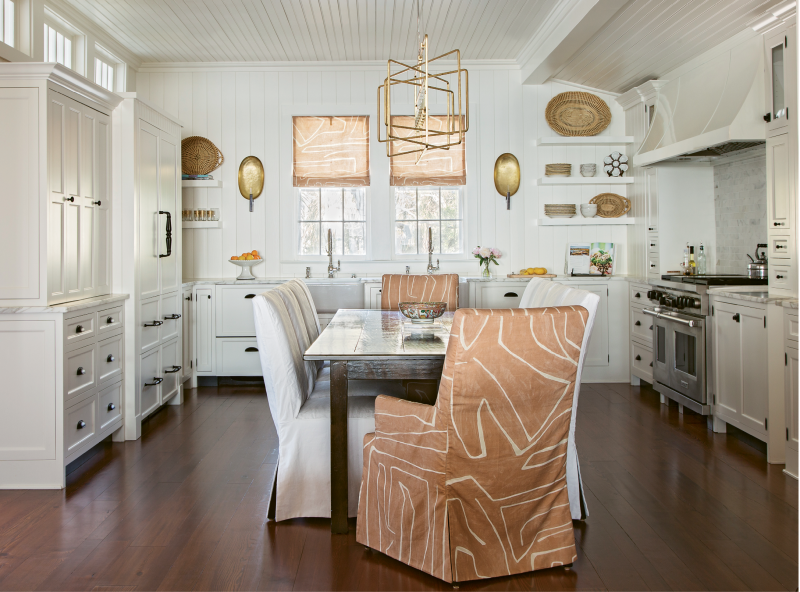 GOLDEN TOUCH: In the kitchen, simple roman shades in an abstract Kelly Wearstler fabric and clean-lined open shelving are offset by dramatic hammered-gold sconces. Instead of an island, the room is anchored by a custom dining table and comfy slip-covered chairs.