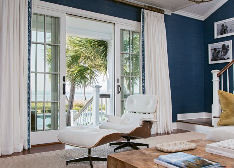 ARMCHAIR TOURISM: Strategically positioned near French doors that lead to the patio, this Eames lounge chair and ottoman provide a sleek yet comfy perch for taking in views of the pool and the Atlantic.