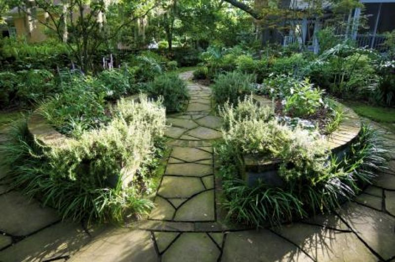 """Well-Rounded: This raised garden is the centerpiece to the four garden rooms. The joints between the bluestone pavers were left """"tooled"""" (ungrouted) to allow for moss or plant growth."""