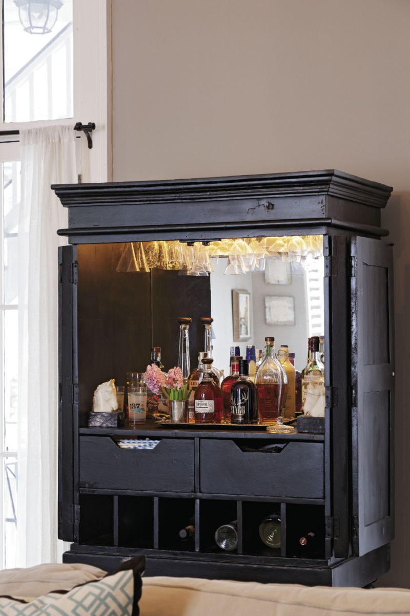 HIGH PROOF A repurposed highboy with mirrored back is well-stocked with all-things Kentucky, i.e. bourbon.