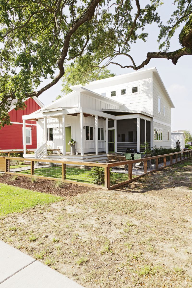 Shiplap and board-and-batten help the modern home blend into the cottage-dominated neighborhood, while a simple wood-and-wire fence keeps the yard looking clean and uncluttered.
