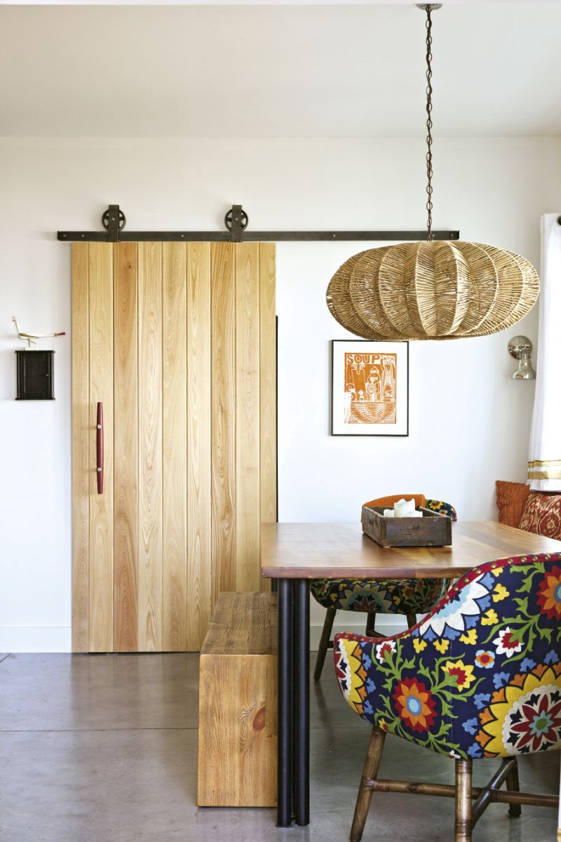 In the dining nook, a space-saving built-in bench pairs with chairs upholstered in funky fabric.