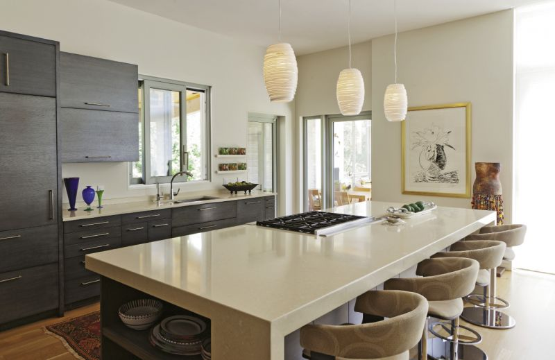 The addition encompasses an open living, dining, and kitchen space, which fosters a loft-like feel. A neutral color palette ensures the interior design complements the stunning views and prized artworks, like the black-and-white Andy Warhol in the kitchen.