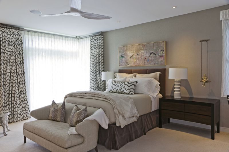 The palette is neutral, but textured wallpaper and drapes in patterned fabric by Donghia make a statement in the master bedroom.