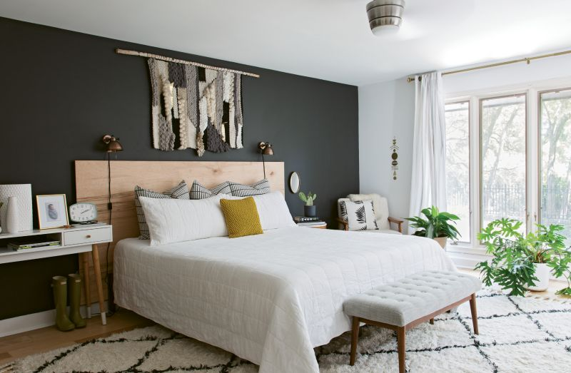 """In the master bedroom, a weaving Erin made with her mom pops against a charcoal accent wall. """"My mom is very artistic, and I had just gotten a new loom, so we were experimenting. Once we finished the piece, I listed it to sell and went to sleep; when I woke up the next morning, I took it down and kept it for myself!"""""""