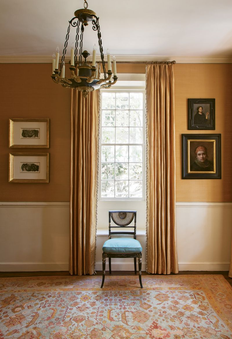 In the foyer, apricot-hued silk wall coverings and coordinating curtains provide an elegant backdrop for a pair of works by mid-century German Expressionist painter Otto Neumann and portraits by contemporary classical realists Daniela Astone and Charles Weed.