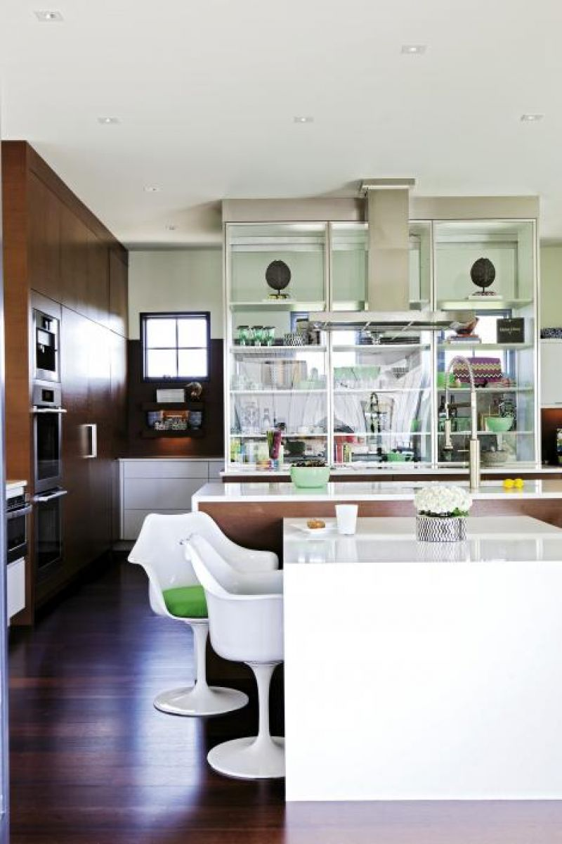 Modern Family: The kitchen features wenge cabinetry, high-gloss Caesarstone countertops, and Saarinen-inspired tulip armchairs.