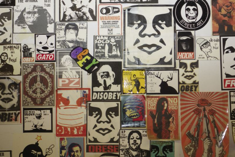"and a close-up of sticker graffiti in a public bathroom, including Fairey's ""Obey Giant."""