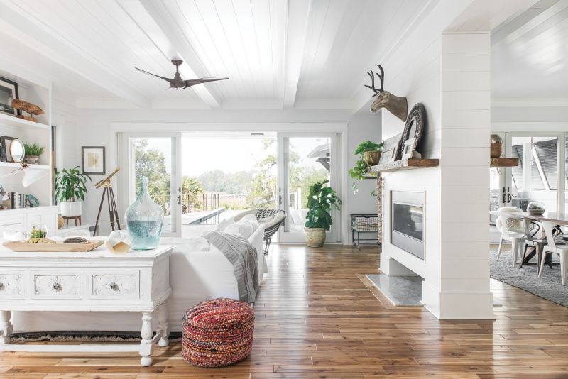 White Out: Melissa describes her home style as clean-lined and coastal. All-white built-ins and furnishings in the living room feel fresh, while acacia wood floors warm the neutral palette. In the otherwise open layout, a wraparound fireplace helps to create distinct zones for lounging and eating.
