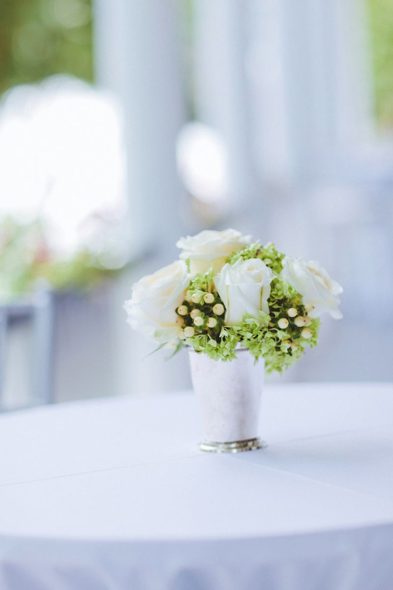 WHITE DELIGHT: White roses, hydrangea, and hypericum berries were placed in mint julep cups for delicate centerpieces.
