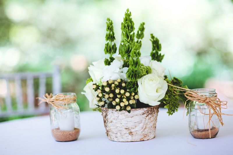 DAINTY DOES IT: Petite groups of Belles of Ireland, white roses, and hypericum berries were bookmarked by Mason jars filled with sand and votive candles.
