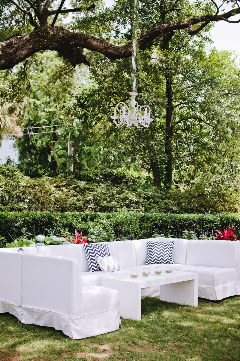 GARDEN PARTY: White sofas from Snyder Event Rentals were dressed up with chevron and ikat-patterned pillows. Loluma camouflaged chandelier chains with fabric and twisting vines.