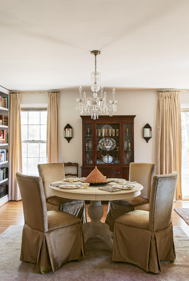 DINING IN STYLE: Velvety gold skirted dining chairs, a 1950s crystal chandelier, and mirrored sconces make the dining nook feel glamorous, while a handed-down hutch nods to tradition.