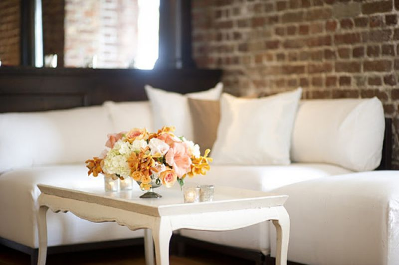 TALK OF THE TABLE: Floral arrangements stood against white sofas and tables and the exposed brick walls of the Historic Rice Mill House.