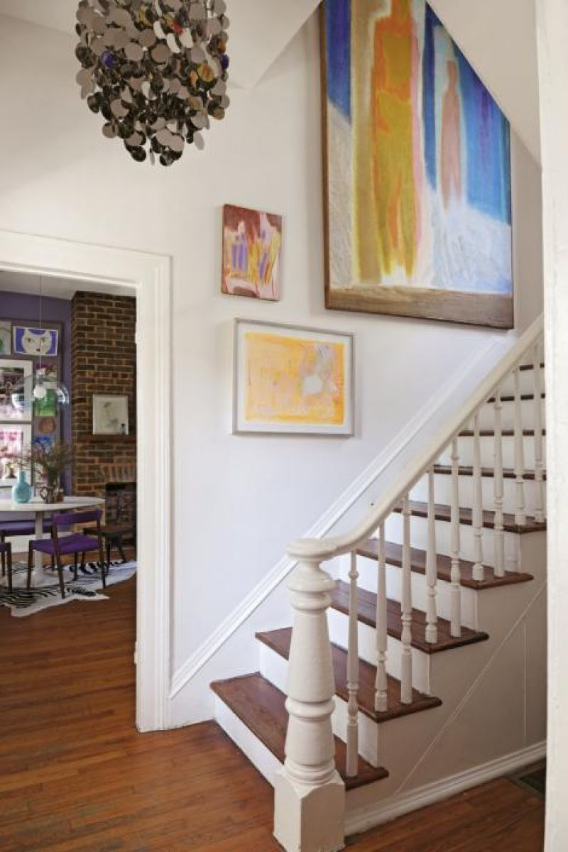 Mid-century art by P.R. McIntosh and others light the stairway with fluorescent color. The 1960s chrome disc chandelier is by Verner Panton.