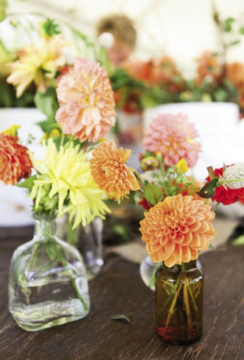 HAPPY HUES: Colorful dahlias tucked into vintage bottles softened the otherwise black and white palette.