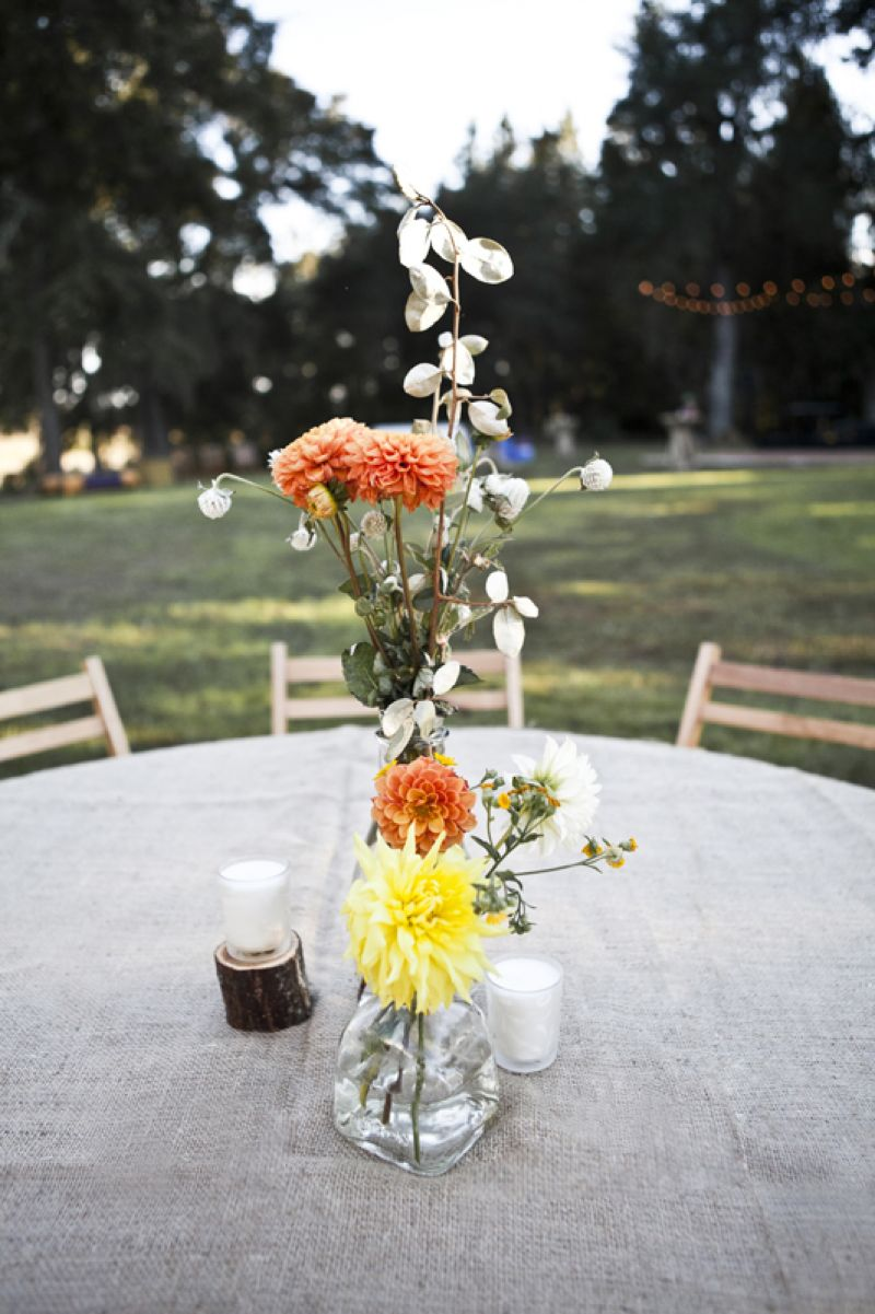 STUNNING SET: Burlap-covered tables were brightened by dahlias and accented with votive candles set at various heights.