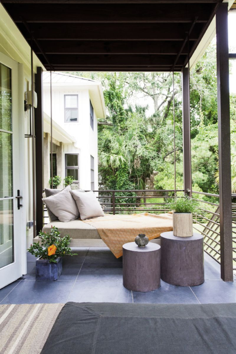 A daybed is suspended from a corner of the kitchen porch and overlooks the grassy backyard.