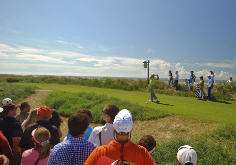 After saving par on the par 3 17 Tiger crushes his drive on 18 with the Atlantic and a few people watching.