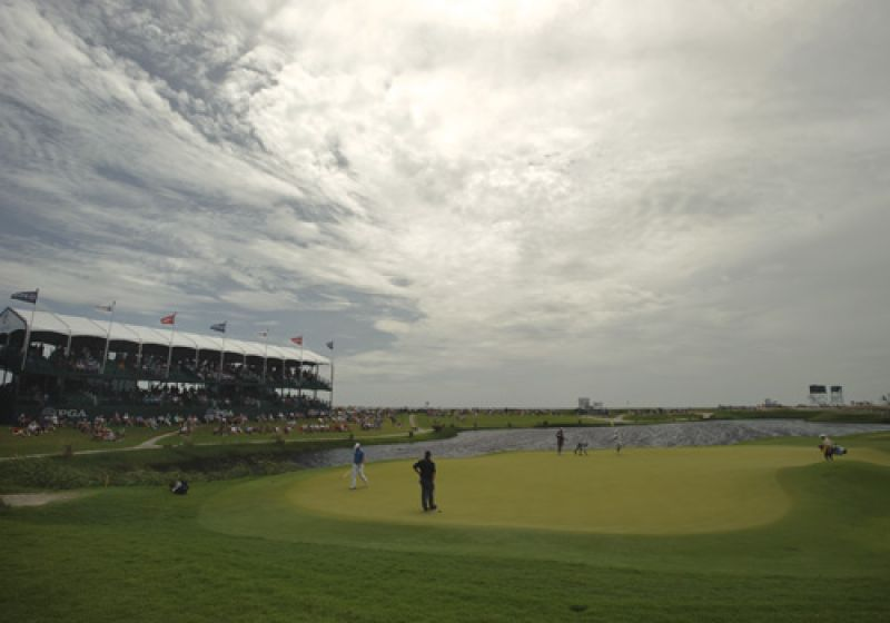 Fans surrounding the 17th green under an ominous sky.