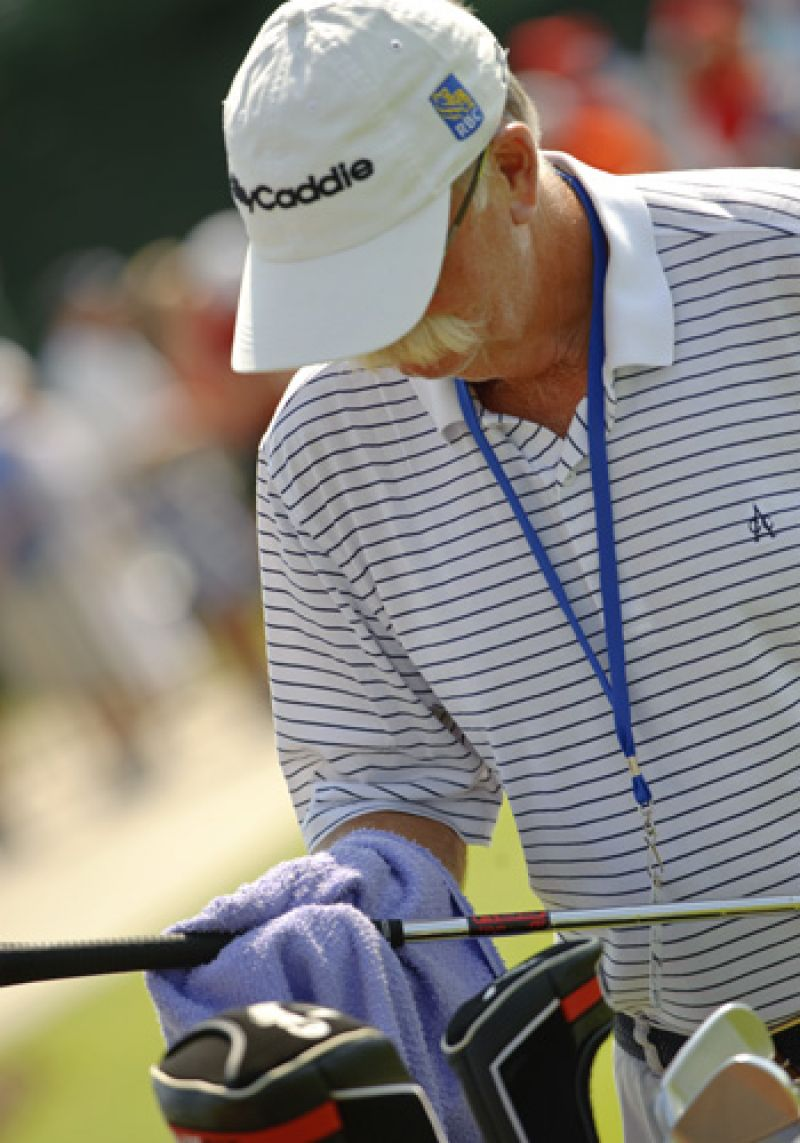 Legendary caddie Fluff preparing Jim Furyk's clubs for the day.