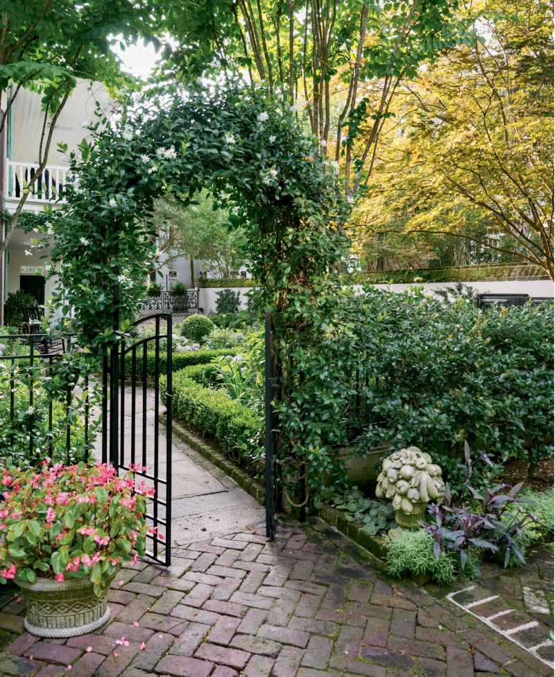 A gate and an arbor covered in confederate jasmine lead the way to the rear courtyard garden.