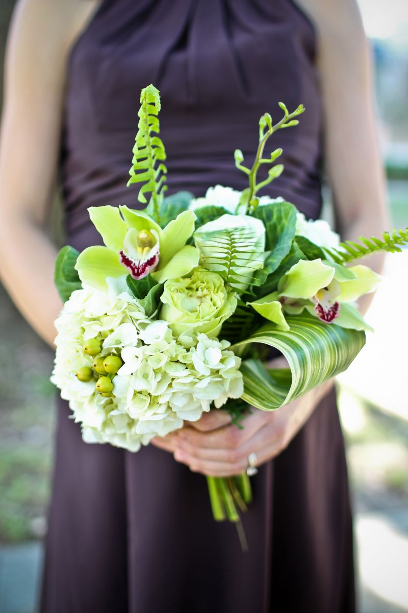 FRESH EFFECT: Jennigray Hewitt of RiverOaks mixed hydrangea, hypericum berries, large variegated ti leaf, and fern for an earthy green bridesmaid bouquet. Orchids added small pops of purple to coordinate with the attendants' frocks.