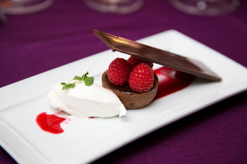 The meal ended with a dessert featuring a chocolate salted caramel tart and fresh raspberries.