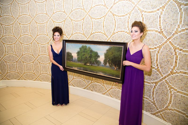 Models showed off a painting up for auction by featured artist Christopher Groves