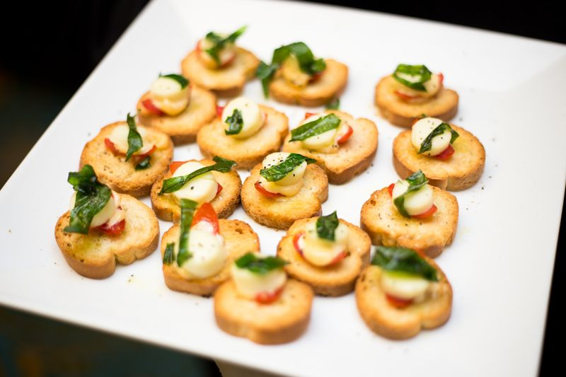 Caprese assemble on artisan crostini, topped with fired basil leaf