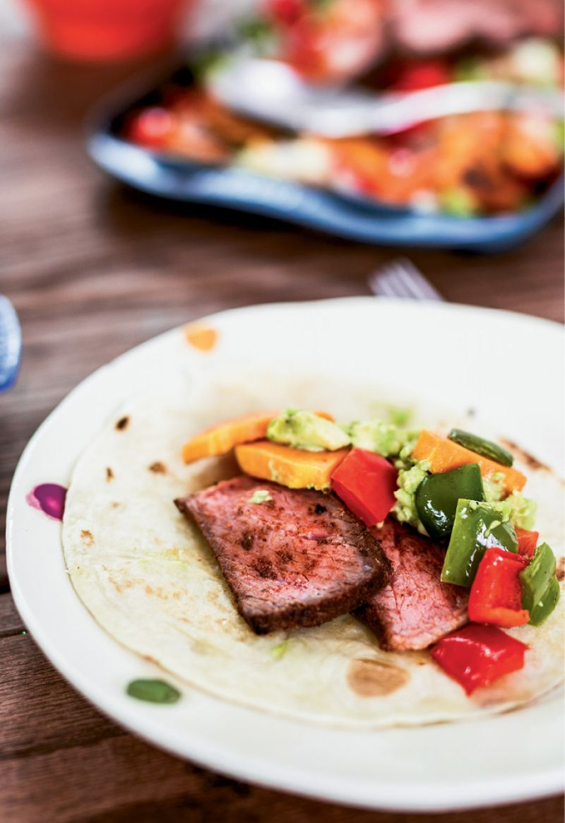 Freshly made tortillas are filled with seasoned beef, squash, peppers, and guacamole.