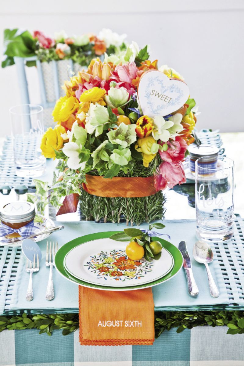 POLISHED PLACESETTING: Anne placed boxwood mats from Jamali Garden on the table, then topped those with glass from Charleston Architectural Glass Studio. She then fashioned florals from coral begonia, bird's nest fern, green hellebores, variegated ivy, chartreuse phalaenopsis orchids, orange and gold ranunculus, rosemary, and tulips. Simple bands of Thai silk ribbon accented the arrangement and bouquet.