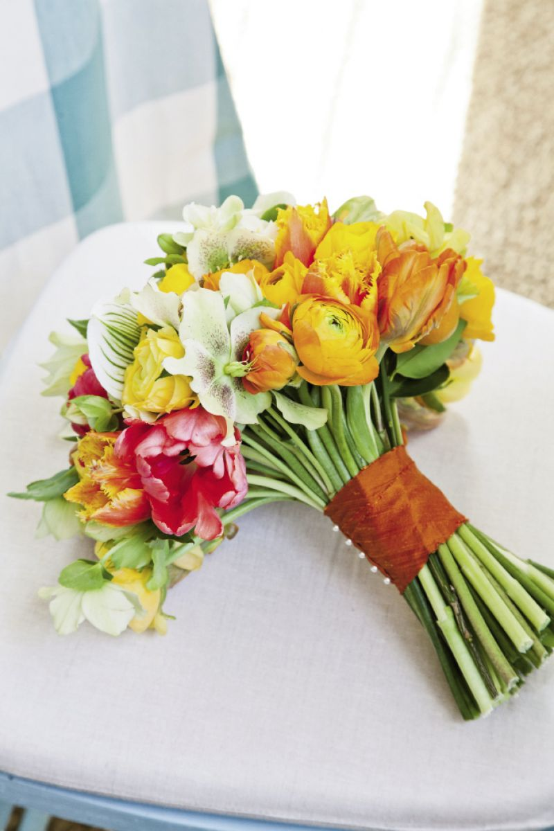 BRIGHT IDEA: coral begonia, bird's nest fern, green hellebores, variegated ivy, chartreuse phalaenopsis orchids, orange and gold ranunculus, rosemary, and tulips made up the bouquet.