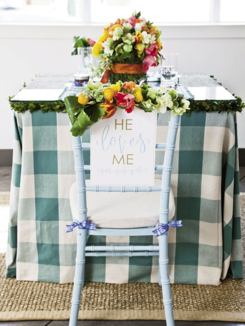 "SIGN OFF: ""He/She Loves Me, yeah, yeah, yeah"" signs by Hardink Calligraphy and dodeline designs hung on the couple's chairs."