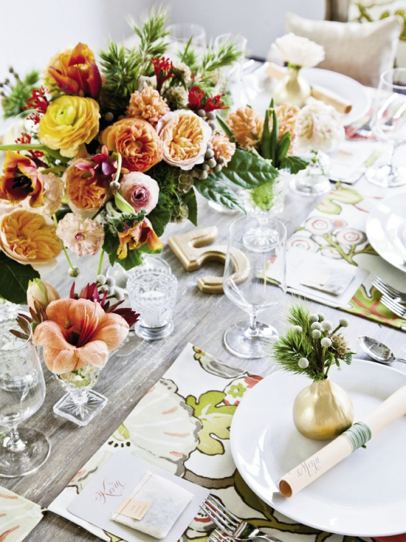 "SET UP: the team fell for a swatch of peach and coral fabric (""Hip Floral Sorbet"" from Calico Corners) that inspired the color palette. They sewed place mats, pillows, and Chiavari chair covers in the material, and picked a floral menu to repeat its colors for fresh, organic style."