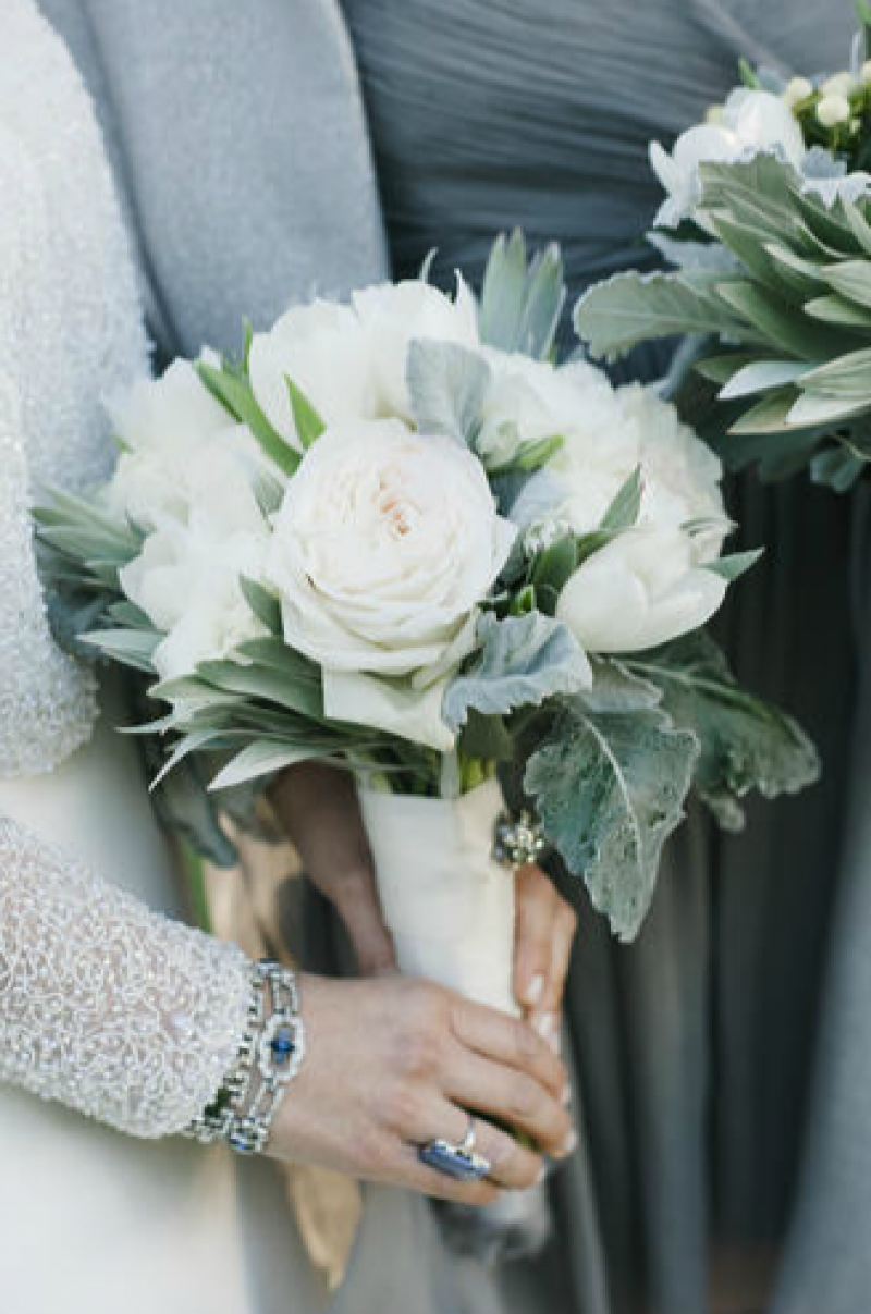 SOFT ACCENTS: A Charleston Bride's Jonie LaRosse fashioned a classic bouquet of white roses, tulips, and lamb's ears to complement Chloe's shimmering bridal jacket.