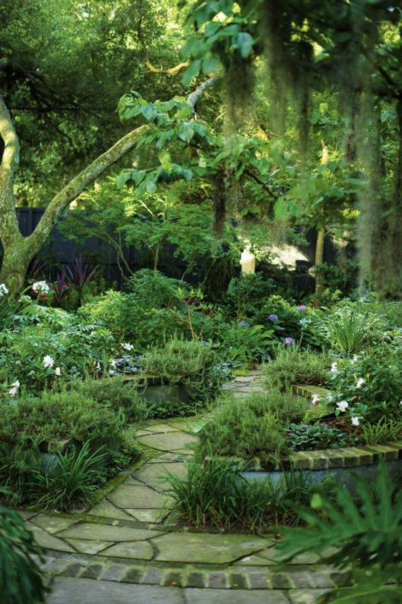 Nice Curves: The circular raised garden was built from six-inch concrete masonry blocks, smooth stucco, and brick and planted with weeping rosemary, salvia, and mandevilla vine.