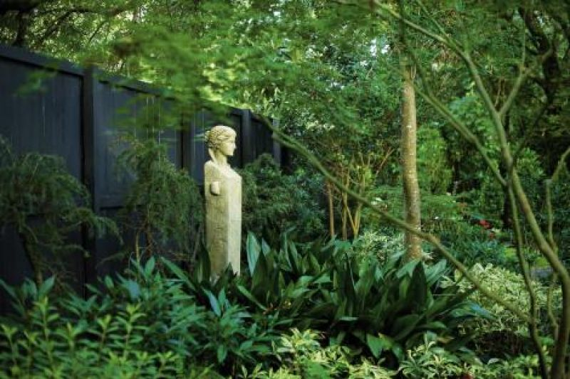 Garden Keeper: Surrounding a maiden statue—one of four, each representing a season—are lush iron plant and deodar cedar.