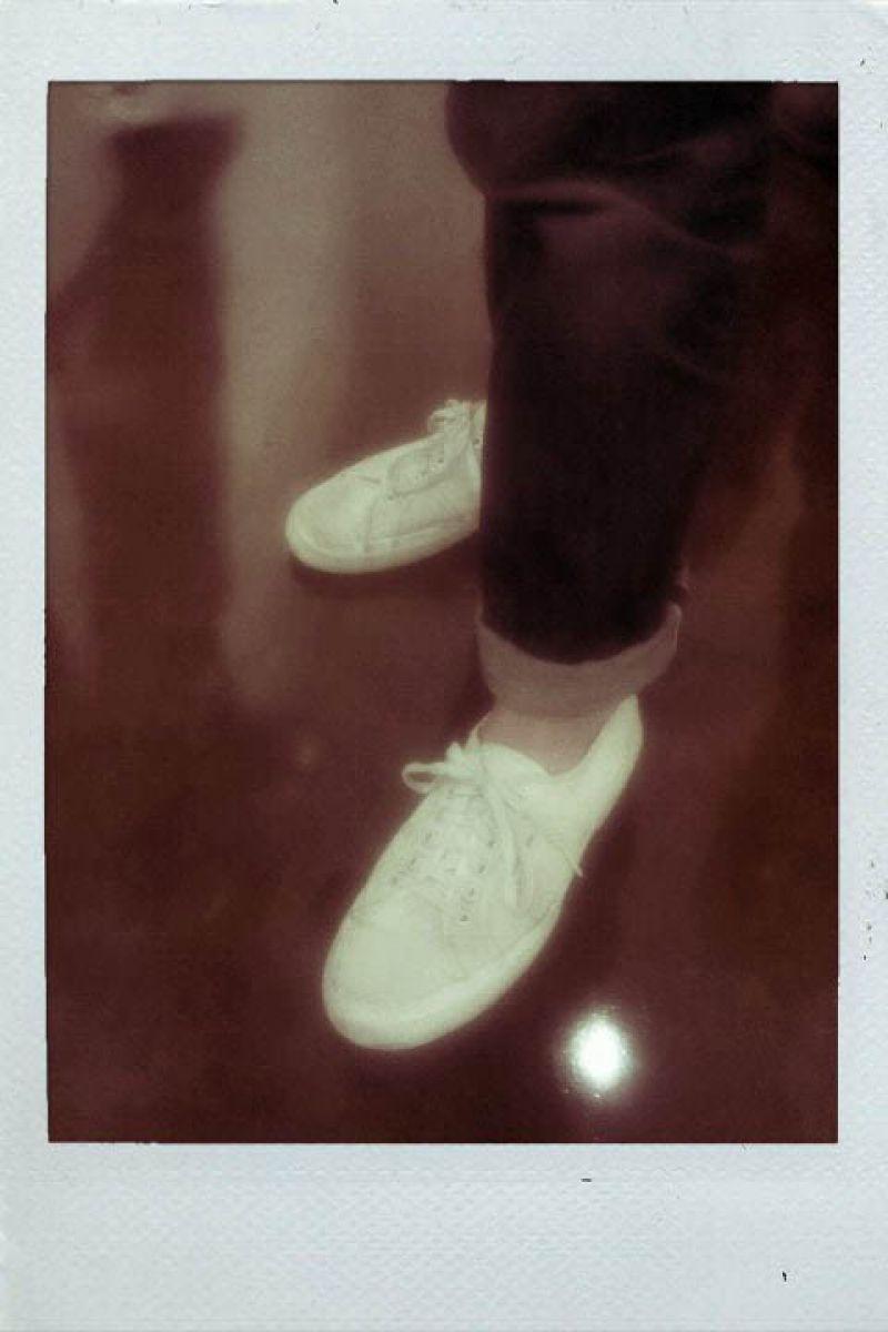 Brett's wears crisp white sneaks with cuffed denim.