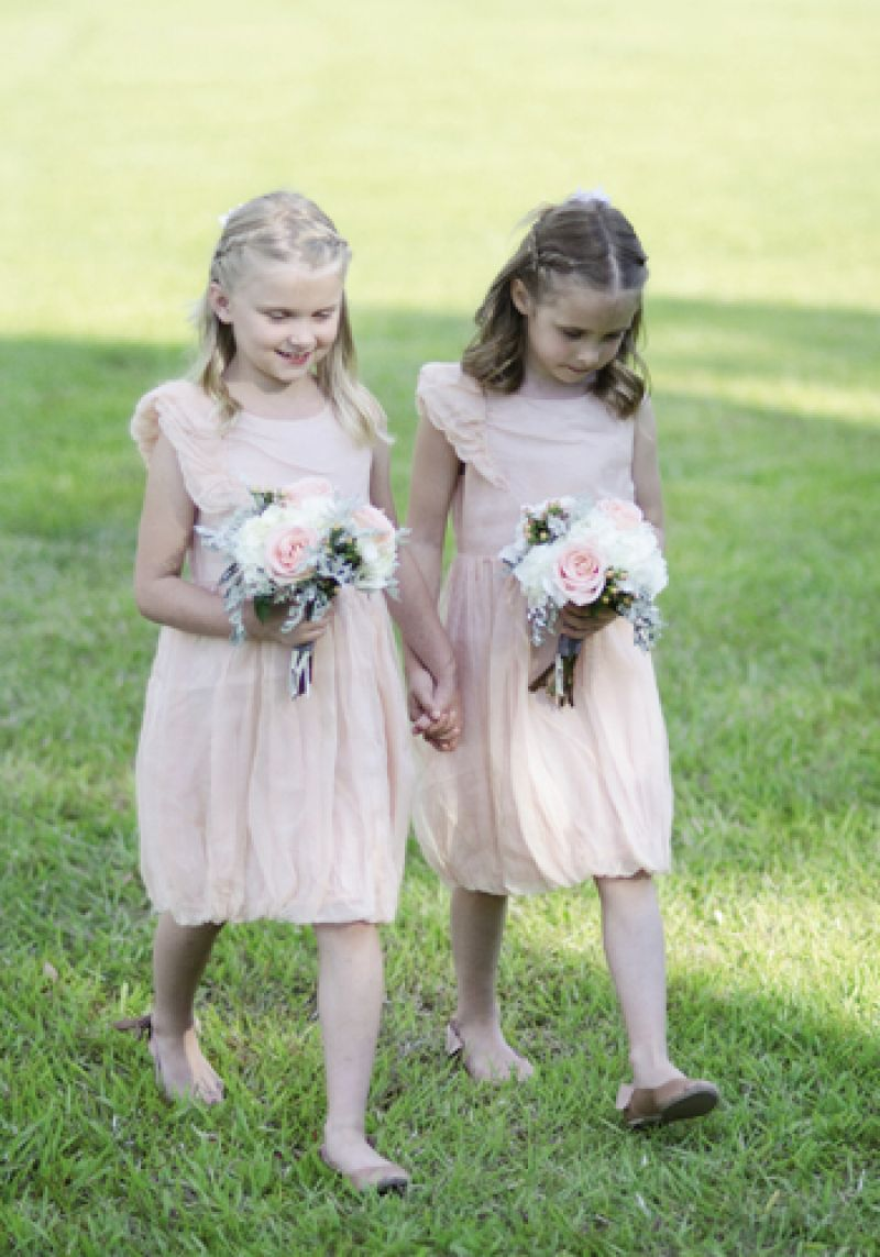 TREAD LIGHTLY: The flower girls carried bouquets that echoed the soft colors of their pale peach attire.