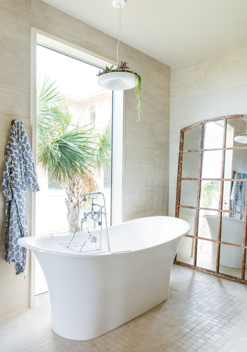In the bath, the large mirror, made from a salvaged window, reflects the beach and the palm trees.