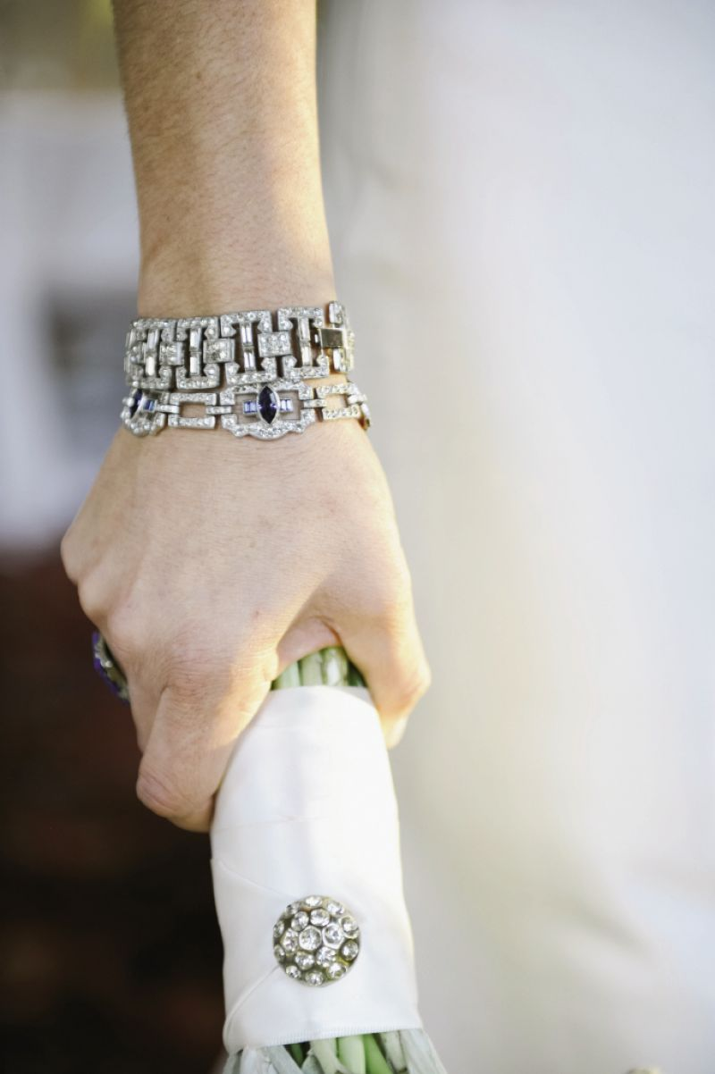"CRYSTAL CLEAR: Chloe paired her vintage gown and jacket with antique Art Deco bracelets, her mother's Art Deco ring, and, of course, her Art Deco engagement ring. ""My mother and I share a love for vintage jewelry, and she searched endlessly to find the perfect pieces,"" says Chloe. A final touch? Pinning the bridal bouquet with a rhinestone brooch that belonged to Chloe's grandmother."