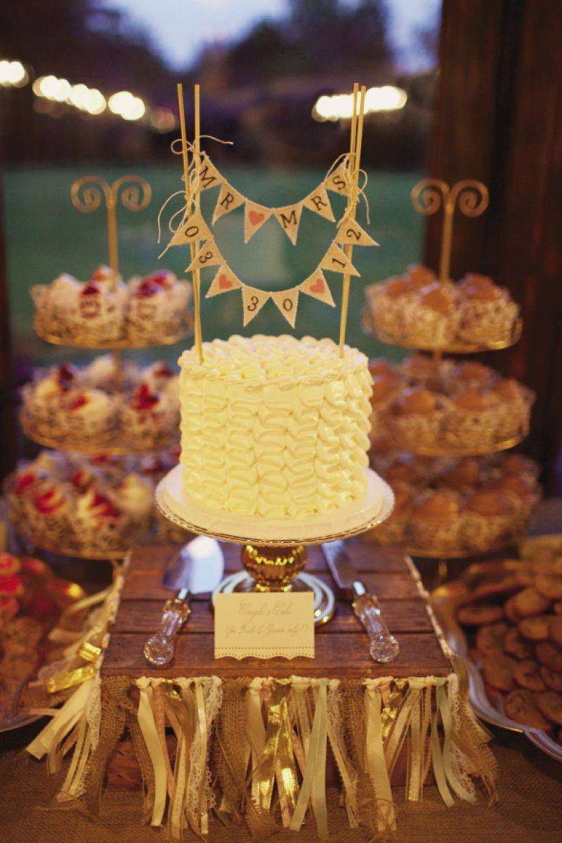 "SIMPLY IRRESISTIBLE: ""Our couple's cake was so good we couldn't bear to leave it in the freezer for a year,"" says Ashton, ""so we ate it when we got back from our honeymoon!"" A cake topper banner accented the confection, while a note told guests it was only for the newlyweds. A garland of ribbons wrapped around a wooden crate took its dais from rustic to romantic."