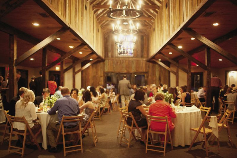 "CARRIAGE HOUSE RULES: ""I loved the wagon wheel chandeliers,"" says Ashton of the carriage house's rustic décor."