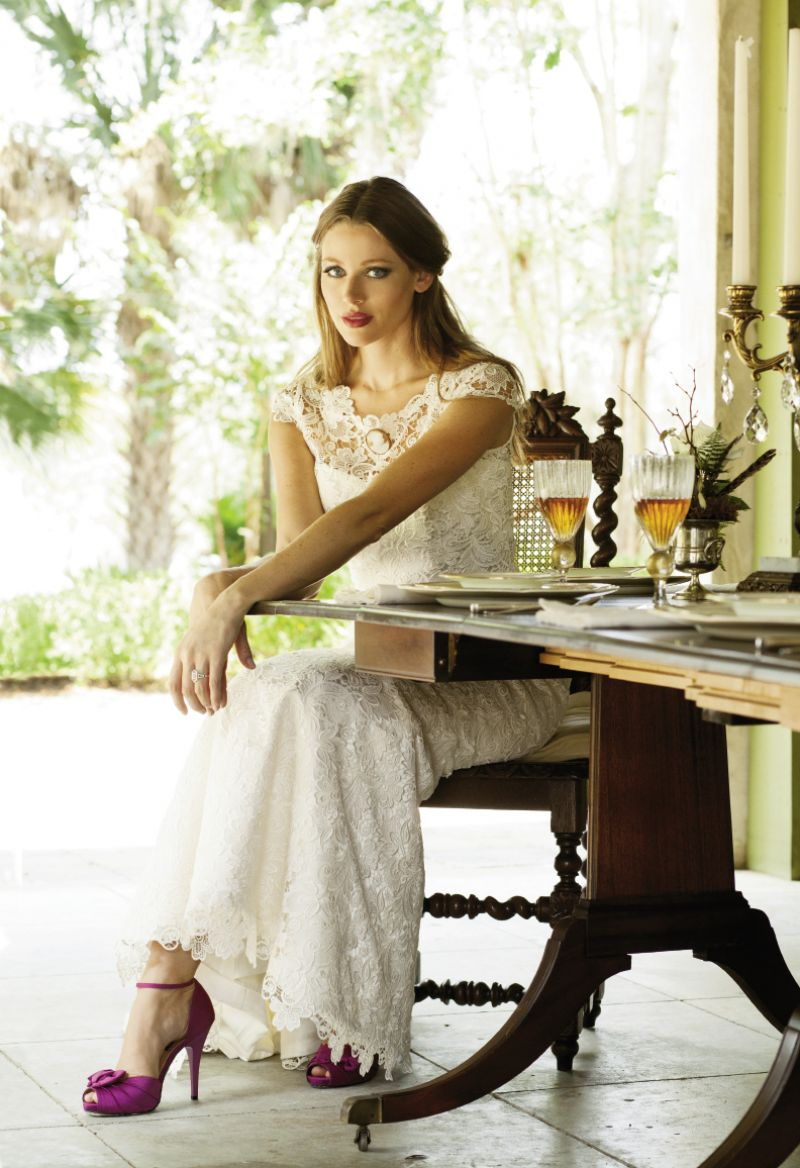 "Callie Tein's  ""Nila"" gown with bateau neckline, cap sleeves, and Italian lace overlay from Modern  Trousseau. Vintage cameo pin from Out of Hand. Nina's d'Orsay heels from LulaKate. 14K  white gold ring  with diamonds from Croghan's Jewel Box. Table and tabletop setting from the personal collection of RiverOaks. Florals by Jennigray Hewitt  of RiverOaks."